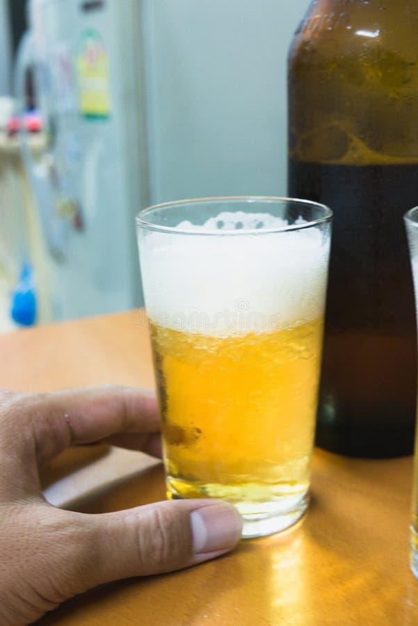 年轻十几岁是愉快在坚苦工作以后饮用啤酒 库存照片