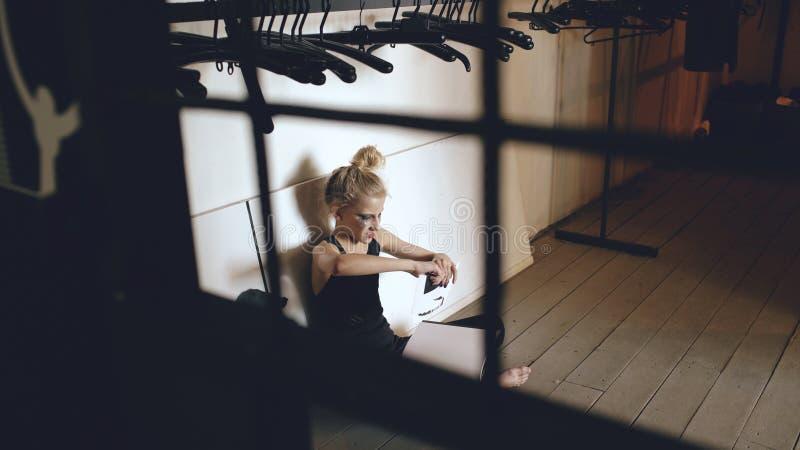 年轻十几岁的女孩舞蹈家哭泣的和撕毁的书坐地板在大厅里户内 免版税图库摄影