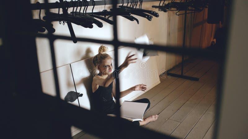 年轻十几岁的女孩舞蹈家哭泣的和撕毁的书坐地板在大厅里户内 库存图片