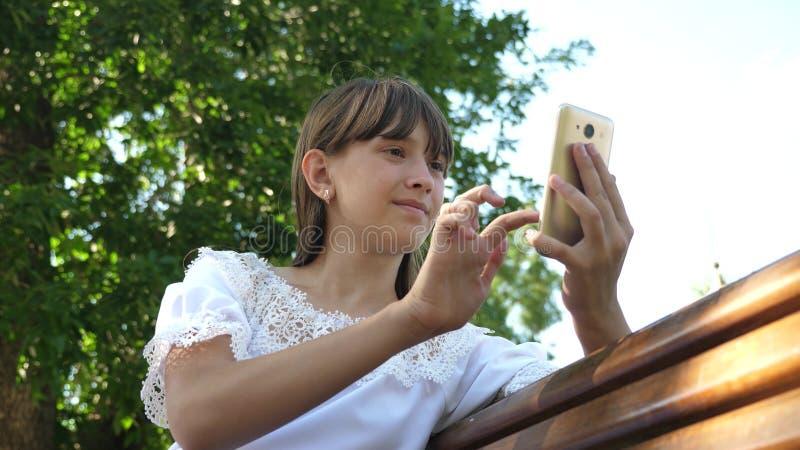 年轻千福年的妇女在树木园,做姿态在电话显示 使用智能手机的少女是 免版税图库摄影