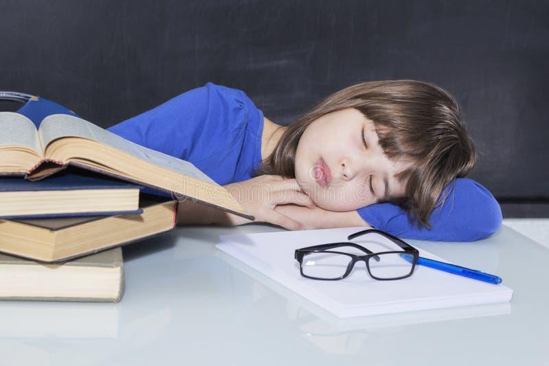 年轻华美的努力女生睡着了在堆她的书,当学习时 免版税库存照片