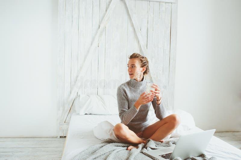 年轻博客作者或女商人在家与社会媒介,饮用的咖啡一起使用在清早在床上 免版税库存图片
