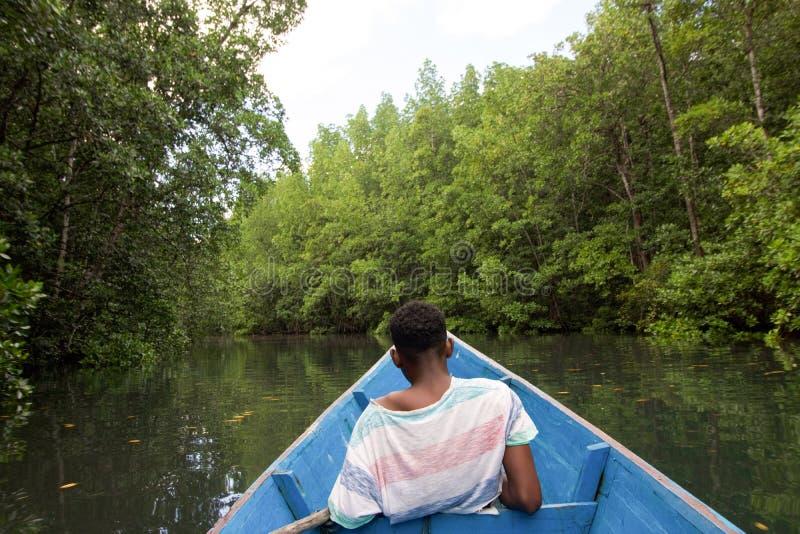 年轻印度尼西亚人坐小船 免版税库存图片