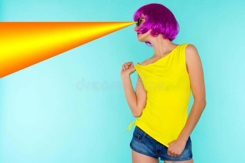 年轻变性妇女和太阳镜,在蓝色背景的黄色T恤杉画象桃红色假发的 库存照片