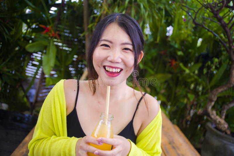 年轻可爱和愉快的亚裔中国女孩获得乐趣在户外喝与秸杆的庭院健康橙汁过去嬉戏 库存图片