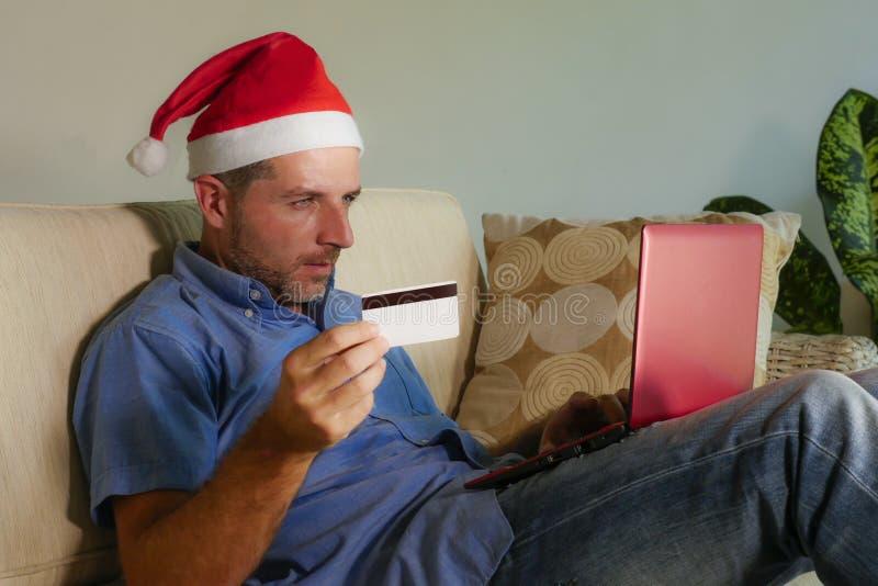年轻可爱和愉快的人在圣诞老人克劳斯使用手提电脑的圣诞节帽子在网上买的xmas礼物和礼物与c 库存图片