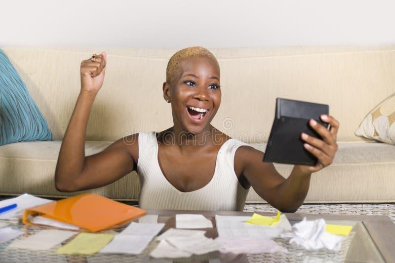 年轻可爱和愉快的成功的黑人美国黑人的妇女微笑的满意的国内会计营业税和付款  免版税库存照片