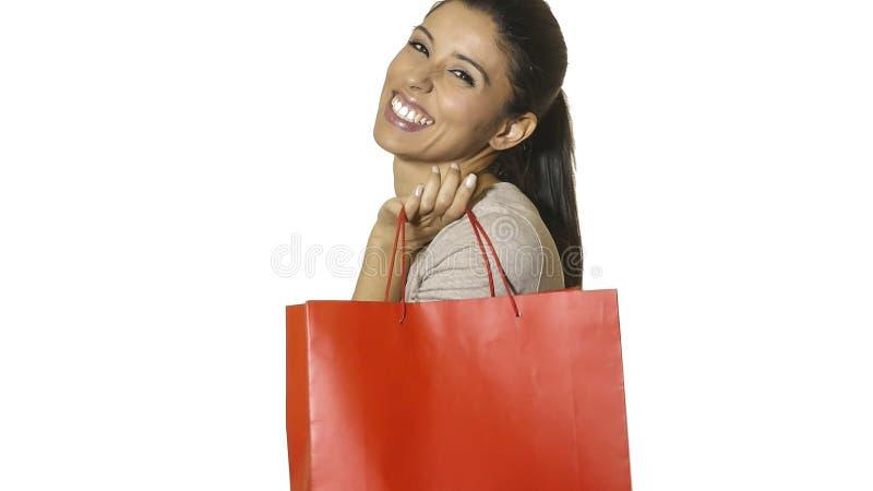 年轻可爱和愉快的拉丁在销售的白色背景隔绝的妇女对红色购物袋微笑负的快乐和正面 免版税库存照片