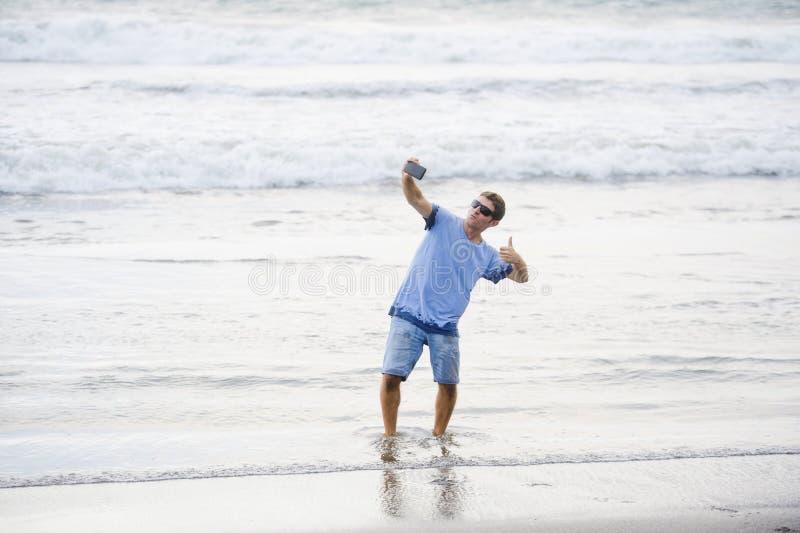 年轻可爱和愉快的白种人30s人获得乐趣在拍与手机微笑的亚洲海滩selfie照片激动  图库摄影