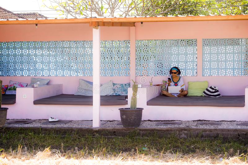 年轻可爱和愉快的行家亚裔妇女与便携式计算机一起使用在放松户外享受成功的工作场所作为int 免版税库存图片