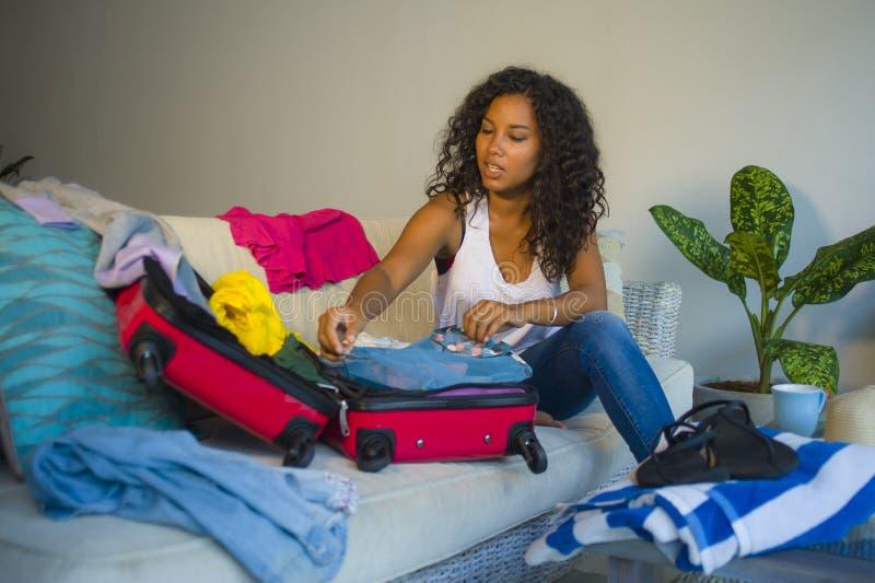 年轻可爱和疯狂的愉快的黑人美国黑人的妇女包装在手提箱的衣裳材料离开为假日做准备绊倒e 库存图片