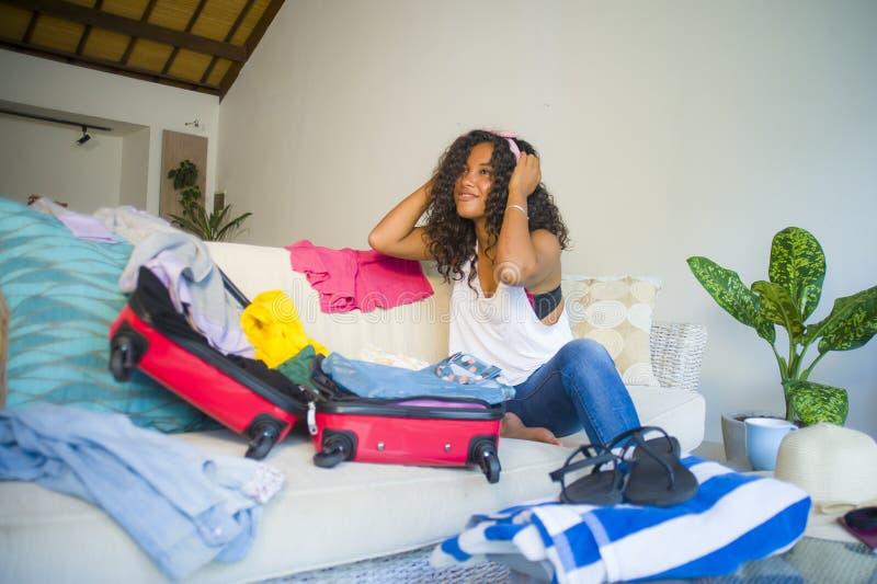年轻可爱和疯狂的愉快的黑人非裔美国人的妇女包装在手提箱的衣裳材料留给为假日做准备三 图库摄影
