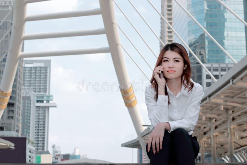 年轻可爱的亚裔女商人正面图谈话在城市大厦的流动巧妙的电话有拷贝空间背景 库存图片