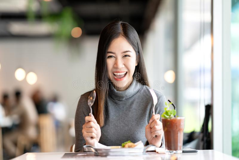 年轻可爱的亚裔感觉妇女拿着叉子的和的匙子看照相机的饥饿,激动,愉快和立即可食的健康食物 免版税库存照片