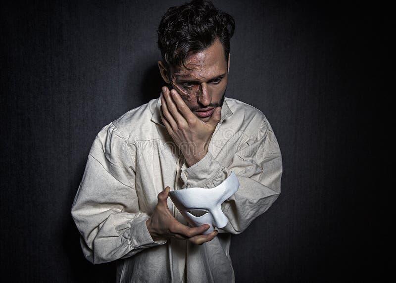 年轻可爱的人以从烧伤的伤痕,拿着象面具的一个白色剧院 免版税库存图片
