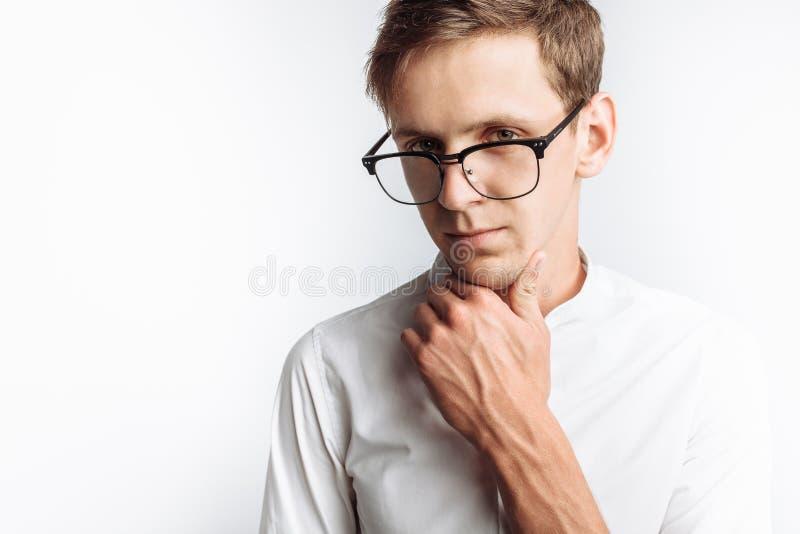 年轻可爱的人画象玻璃的,在白色衬衣,隔绝在白色背景,做广告的,文本插入 图库摄影