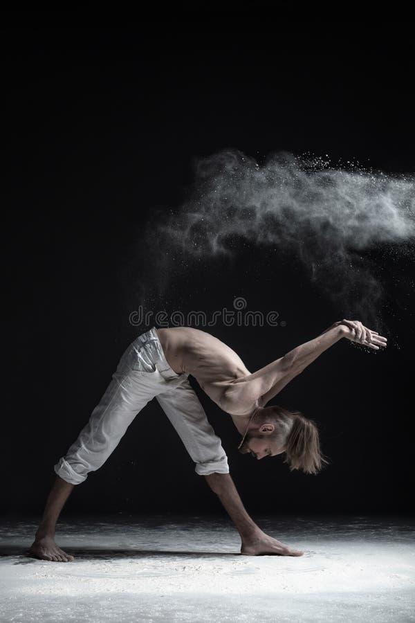 年轻可爱的信奉瑜伽者人实践的瑜伽,站立在Parivrtta Parsvatanasana锻炼,解决 免版税库存照片