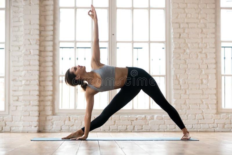 年轻可爱的信奉瑜伽者女子实践的瑜伽在Utthita Trikonasa 免版税库存照片