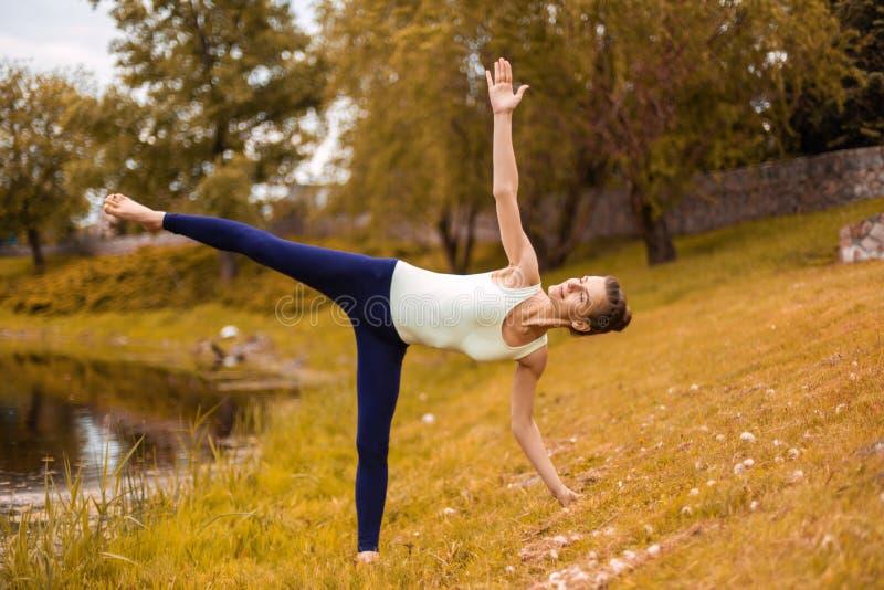 年轻可爱的信奉瑜伽者女子实践的瑜伽,做Utthita Trikonasana锻炼,延长的三角姿势 免版税库存图片