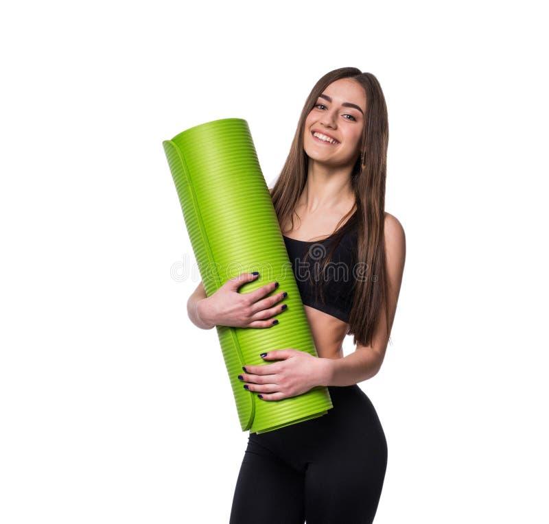 年轻可爱的健身妇女准备好拿着绿色瑜伽席子的锻炼被隔绝在白色背景 免版税库存图片