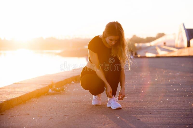 年轻可爱的健身妇女的图片日落背景的 免版税库存照片