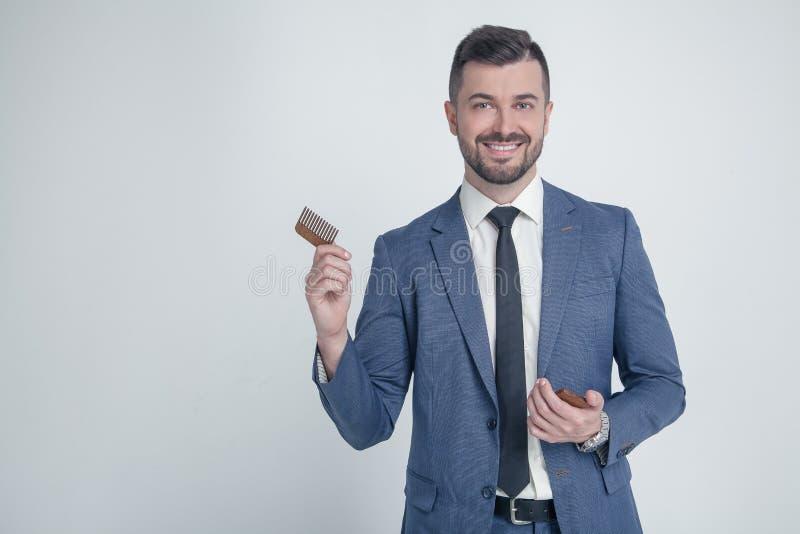 年轻可爱的商人画象与微笑的神色的,拿着木梳子 梳在沙龙的衣服的时髦的有胡子的理发师 库存图片