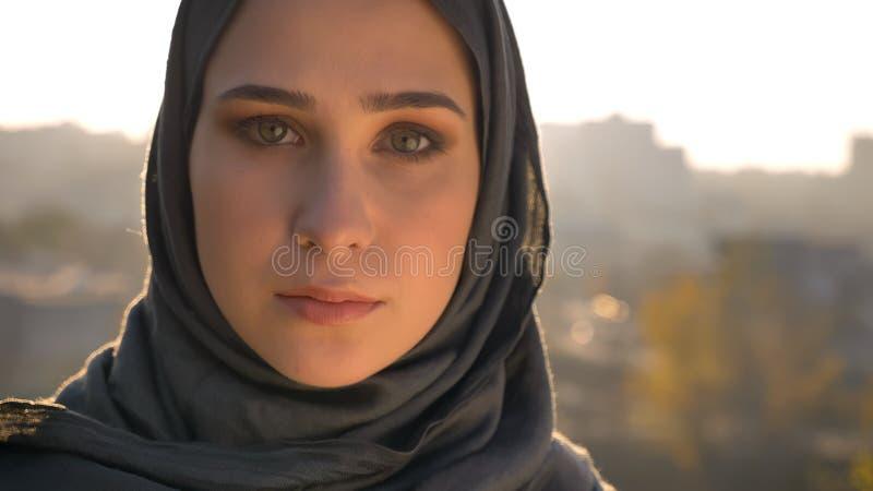 年轻可爱的回教女性特写镜头画象看直接与在背景的城市布局的hijab的 免版税图库摄影