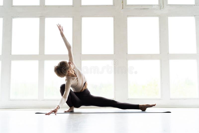 年轻可爱的女子实践的家庭瑜伽,解决,佩带的运动服 健康生活,保留适合的概念 免版税图库摄影