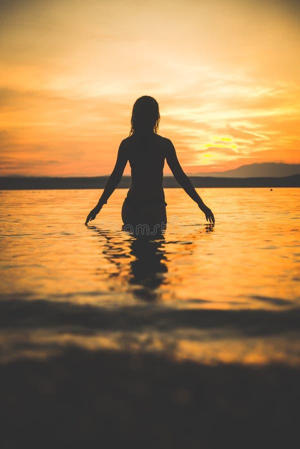 年轻可爱的女孩式样剪影在水中 免版税库存照片