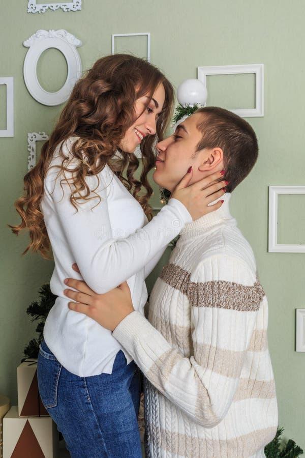 年轻可爱的女孩抚摸她的男朋友的面颊 免版税库存图片