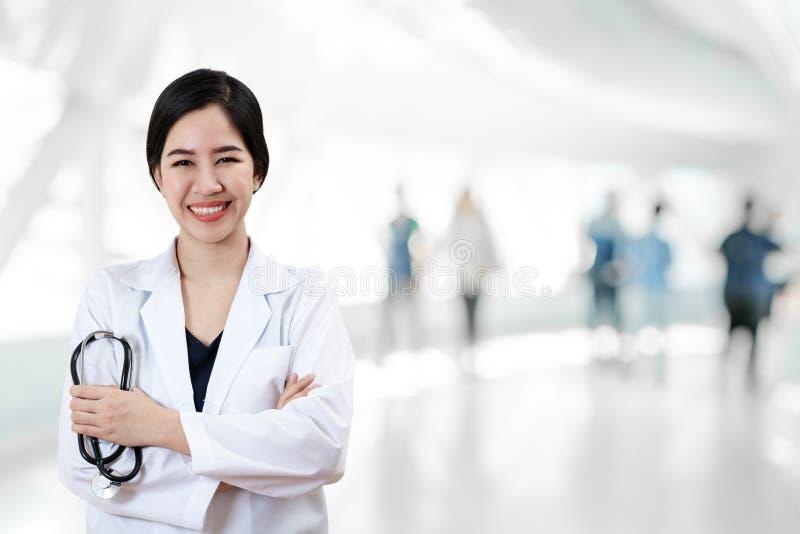 年轻可爱的女性亚裔医生或医师画象横渡了武器储备听诊器医疗设备 免版税图库摄影