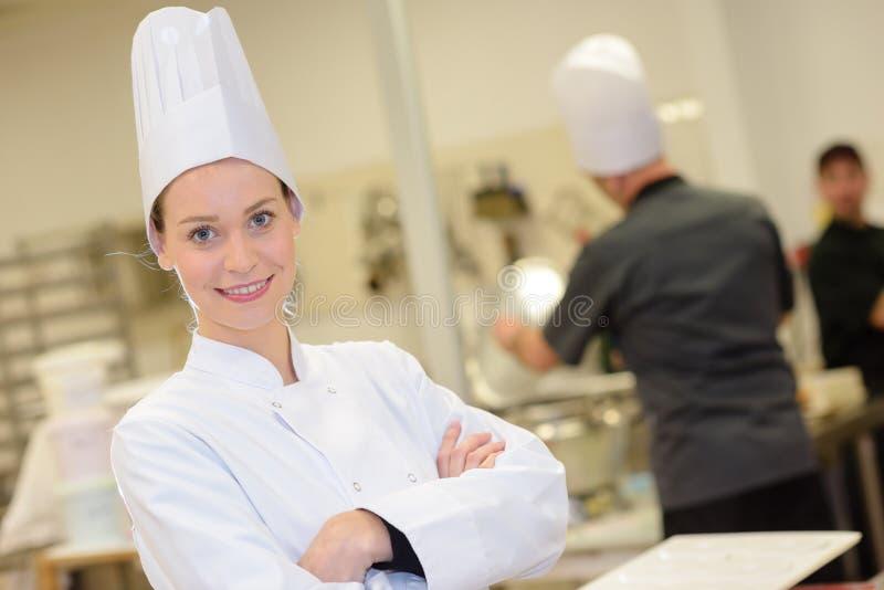 年轻可爱的女性厨师或厨师在工业厨房里 库存图片