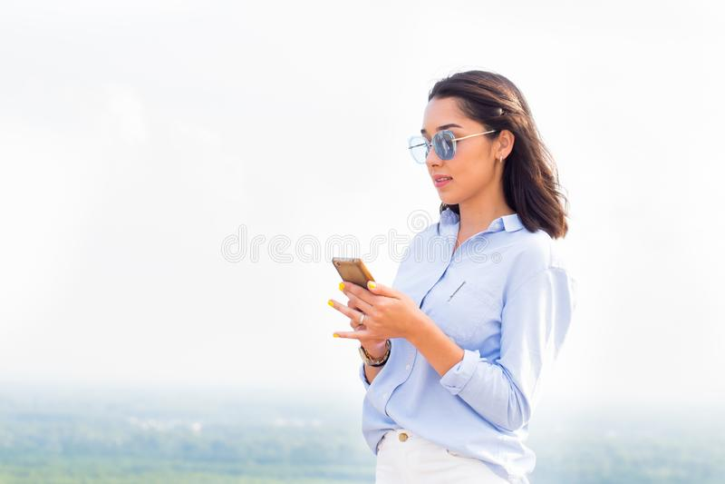 年轻可爱的妇女使用在山和树背景的智能手机  夏天和现代技术 图库摄影