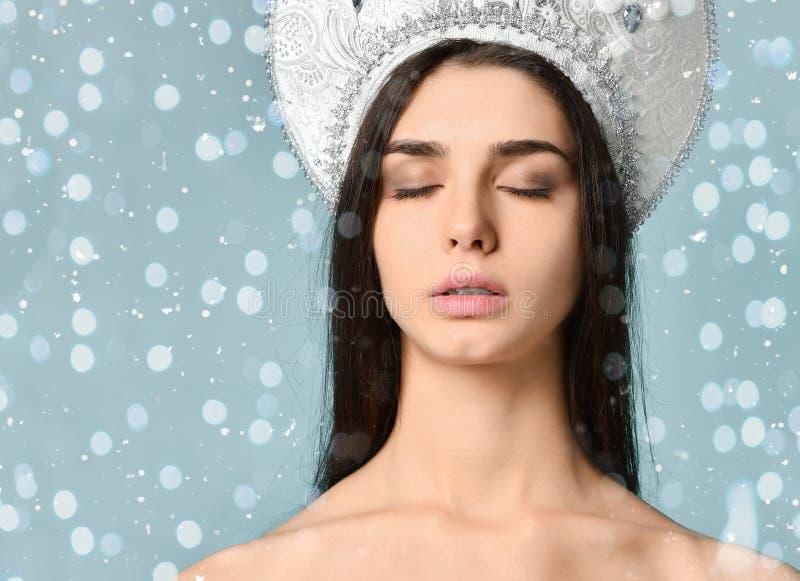 年轻可爱的妇女秀丽画象在多雪的圣诞节背景的 免版税库存图片