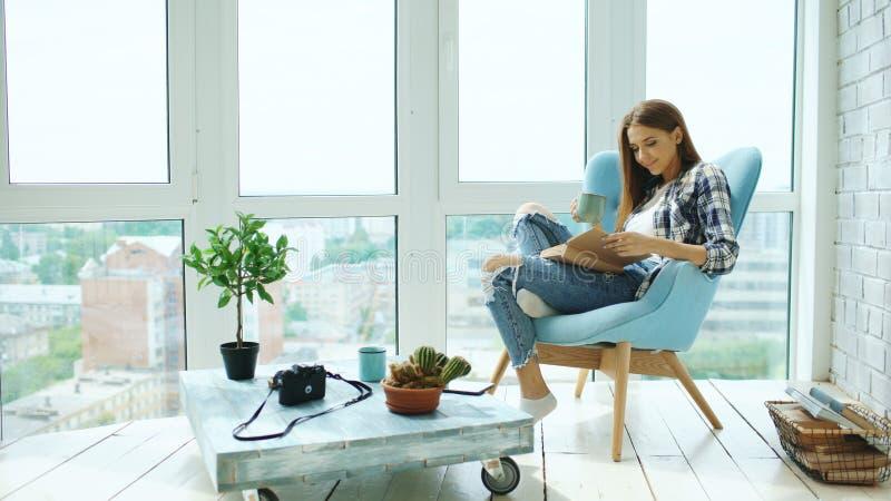 年轻可爱的妇女读了书并且喝咖啡坐现代顶楼公寓的阳台 库存图片