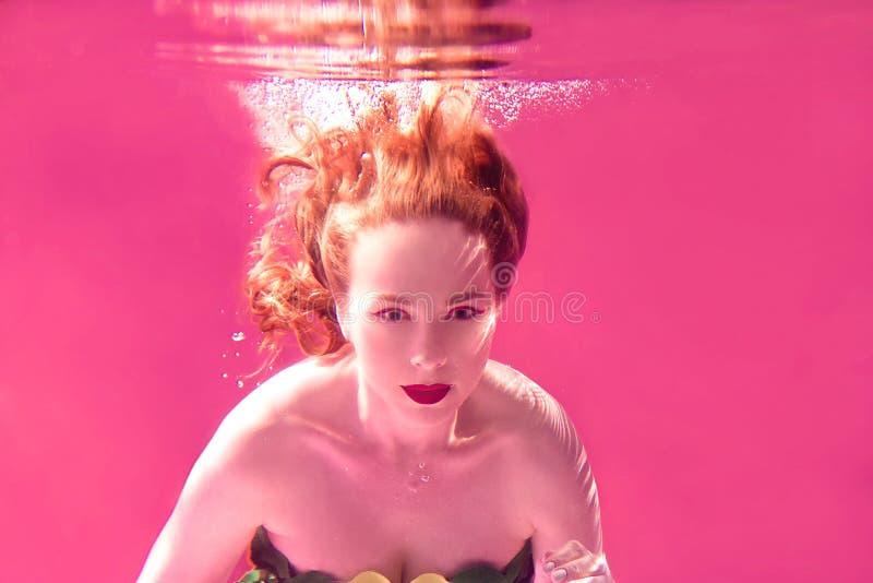 年轻可爱的妇女超现实的画象水下在五颜六色的水中 库存图片