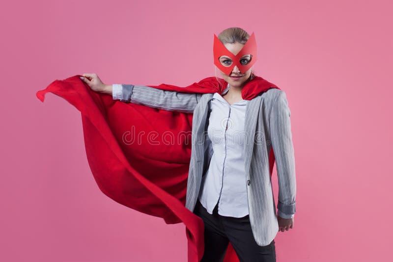 年轻可爱的妇女超级英雄 西装的女孩和与英雄红色斗篷的一个面具  库存图片