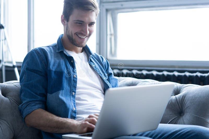 年轻可爱的微笑的人浏览在他的膝上型计算机,在家坐灰色沙发在家,穿偶然服装 库存照片