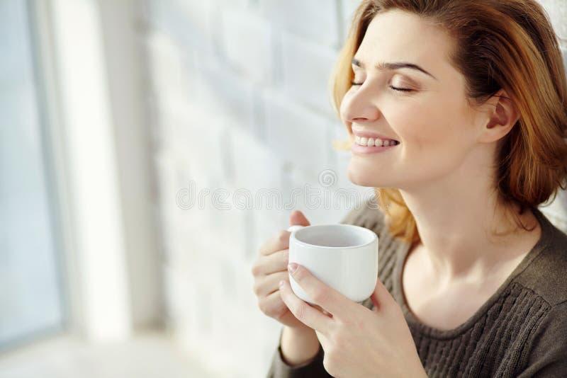 年轻可爱的微笑的妇女画象有一个杯子的早晨咖啡或茶 库存图片