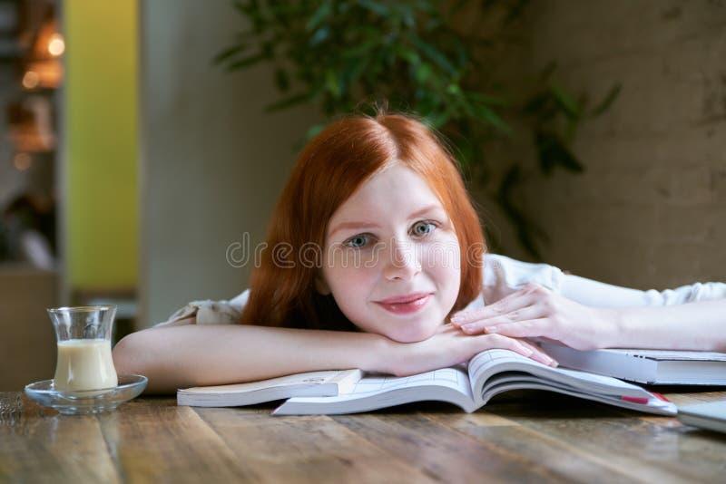 年轻可爱的微笑的学生妇女画象有长的红色的 免版税图库摄影