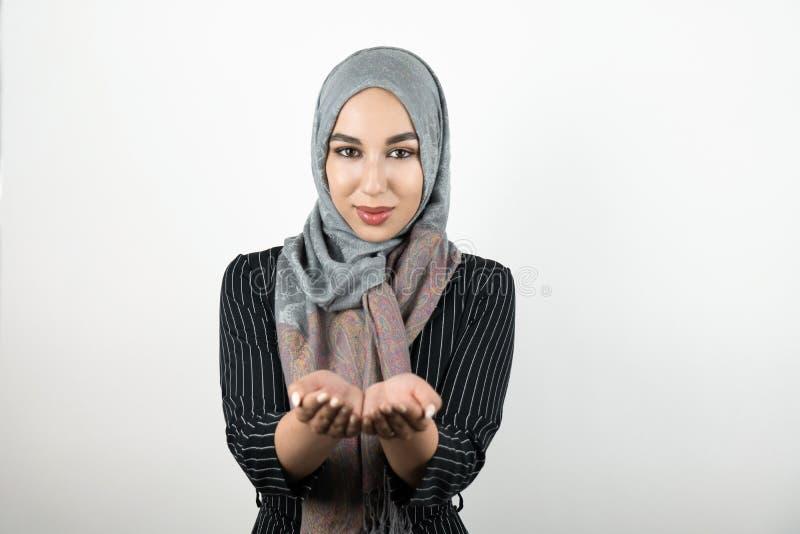 年轻可爱的有希望的回教妇女佩带的头巾hijab,握她的手的头巾一起隔绝了白色 免版税库存照片