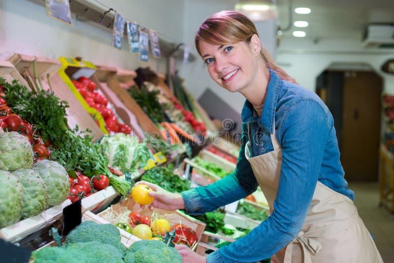 年轻可爱的水果市场女推销员 免版税库存照片