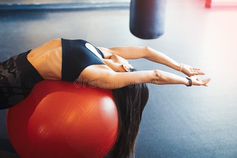 年轻可爱的深色的女孩实践的锻炼和crossfit训练和舒展在橙色fitball 库存照片
