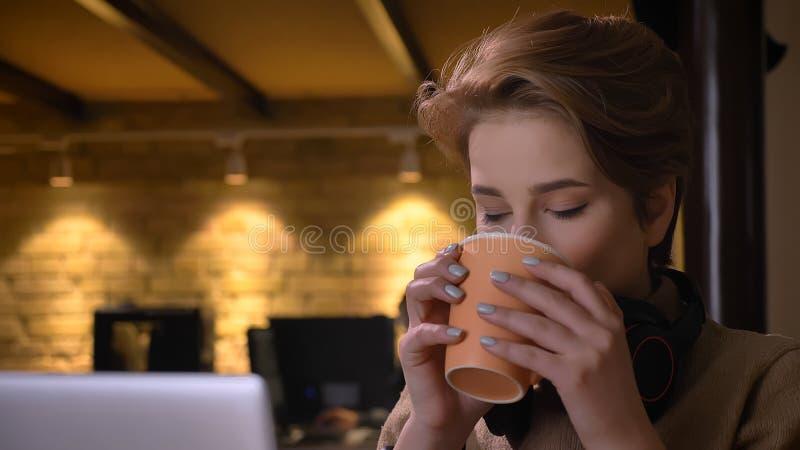 年轻可爱的白种人女实业家特写镜头射击有有的耳机的在膝上型计算机前面的一个咖啡休息 库存照片