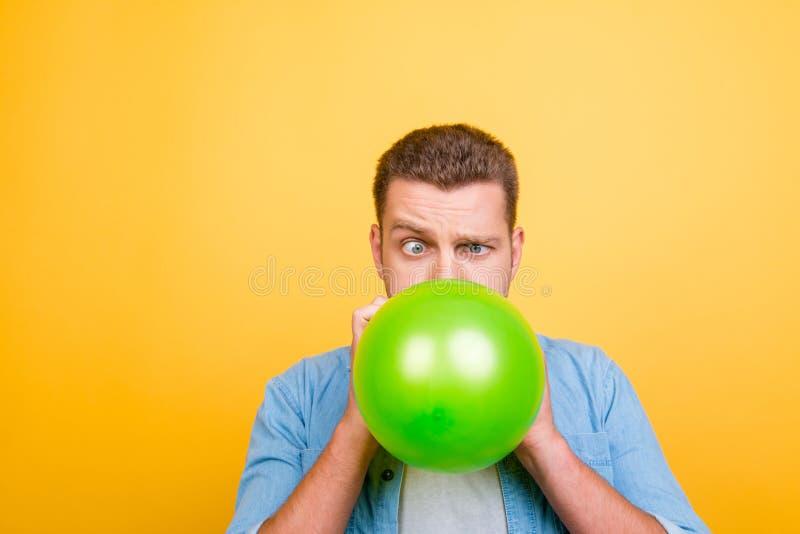 年轻可爱的白肤金发的人疲倦炸毁气球新年pa 免版税库存图片