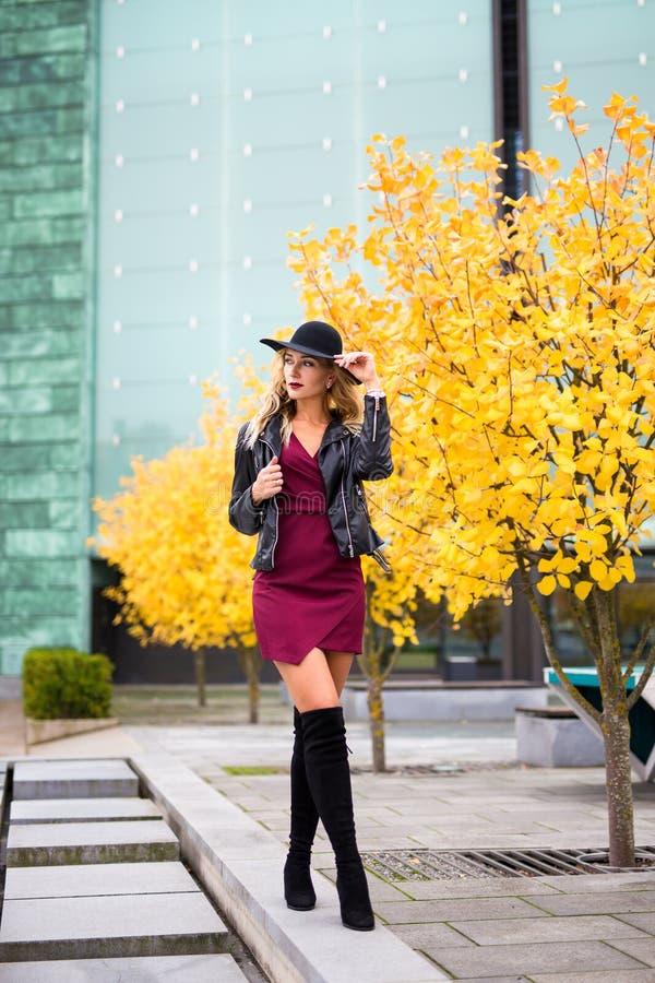 年轻可爱的白肤金发的妇女全长画象在秋天城市 免版税图库摄影