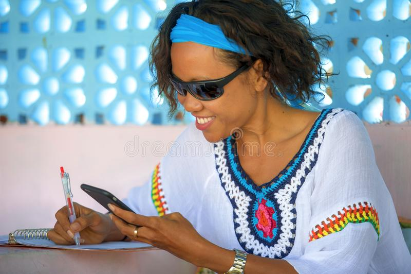 年轻可爱的行家和异乎寻常的看的女孩愉快和轻松使用运作在手机微笑的达的互联网社会媒介 库存照片