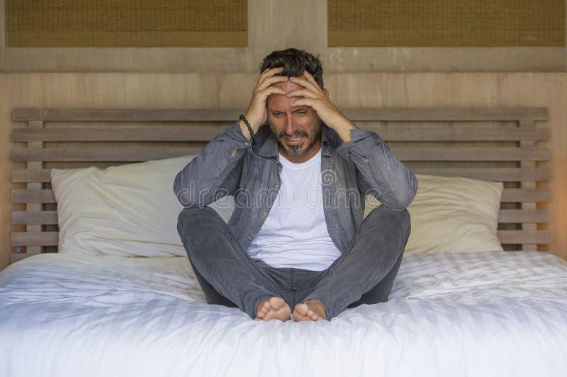 年轻可爱的被淹没的和沮丧的人坐哭泣的床哀伤和沮丧的痛苦消沉危机感觉 免版税库存照片