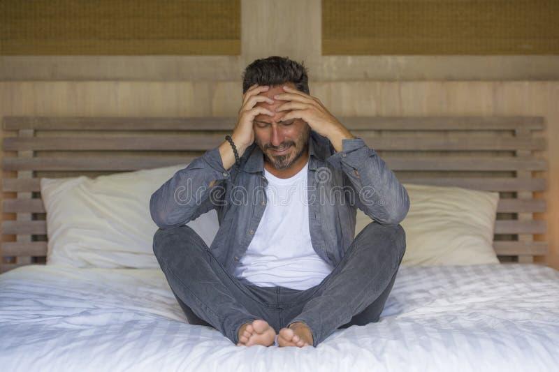 年轻可爱的被淹没的和沮丧的人坐哭泣的床哀伤和沮丧的痛苦消沉危机感觉 库存图片