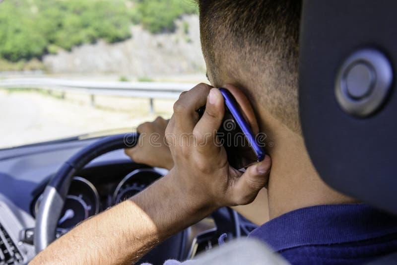 年轻司机,使用智能手机,在汽车的路 免版税库存图片